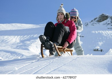 Young woman pushing her friend sitting on a sled in snow