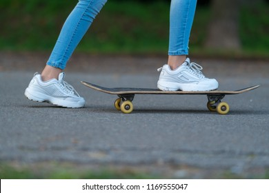 Young woman pushing herself along on a skateboard in a low angle cropped view of her feet on a tarred road
