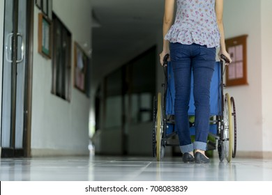 Young woman pushing wheelchair with her disabled patient in Hospital - Healthcare concept
