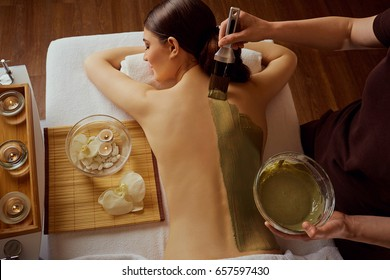 Young woman is put on a mask on her back in  spa salon