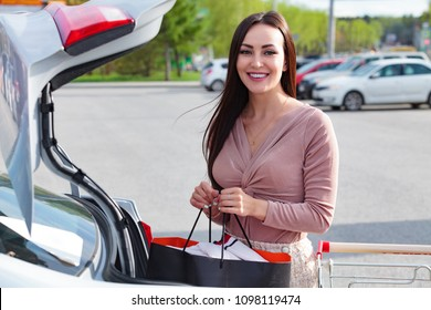Young woman puts bags from the shopping cart to the trunk of a car at the parking.