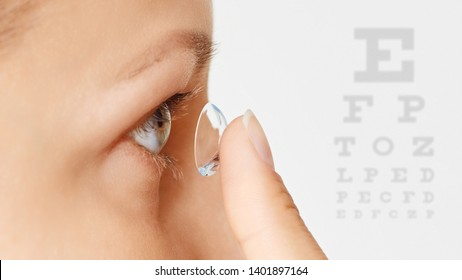 Young woman puts contact lens in her eye over white background. Eyewear, eyesight and vision, eye care and health, ophthalmology and optometry concept. Selective focus, close up