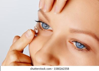 Young woman puts contact lens in her eye over white background. Eyewear, eyesight and vision, eye care and health, ophthalmology and optometry concept, close up