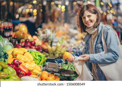 Young Woman puts fruits and vegetables in cotton produce bag at food market. Reusable eco bag for shopping. Sustainable lifestyle. Eco friendly concept.