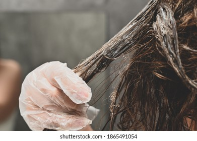 A young woman puts a healing mask on her hair at home. The girl coloring her hair in her own bathroom. Self-care and lifestyle, solving hair issues.