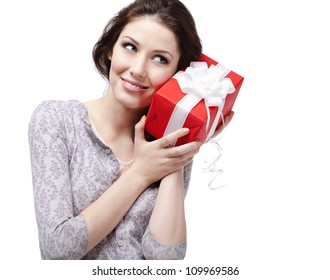 Young woman puts her ear to the present wrapped in red paper, isolated on white