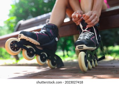 Young woman puts on roller skates in park closeup