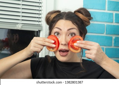 young woman puts tomato slices to the cheeks