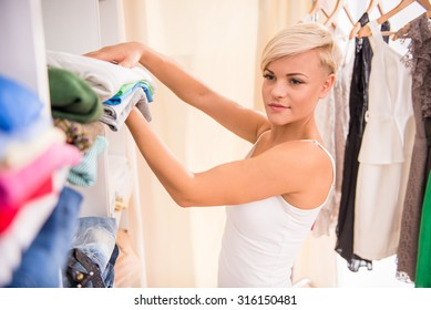 Young woman is putting clothes on the shelves.