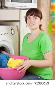 Young woman putting clothes in to washing machine and smiling
