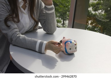Young woman putting coin in piggy bank
