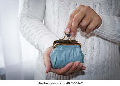 Young woman putting coin in purse. Leather purse for coins.