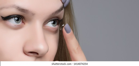 Young woman putting contact lens in her left eye, close up. isolated on gray background.