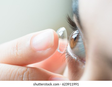 Young woman putting contact lens in her right eye, selective focus on cornea of  the eye.