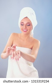 Young woman putting cream on her hand Isolated on gray background. Young woman