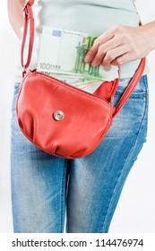 Young woman putting Euro banknotes in a handbag