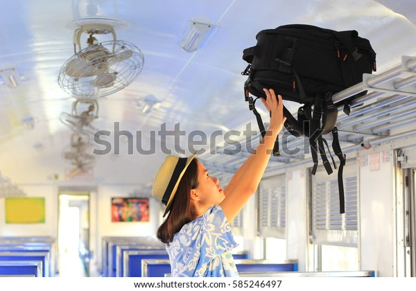 young woman putting her backpack on the top shelf in the train, Summer holiday and travel concept