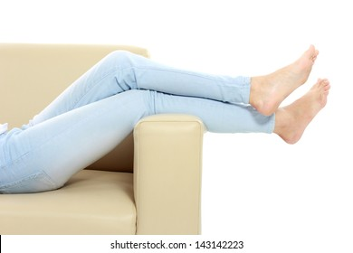 Young woman putting her feet up on sofa