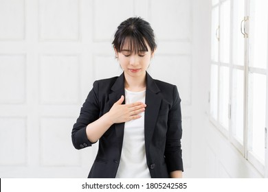 Young woman putting her hands on her chest, shot in the studio