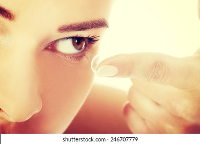 Young woman putting lens into eye.