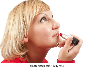young woman putting make up on her face. Isolated