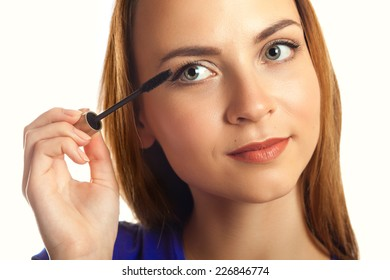 Young Woman putting mascara makeup isolated on white