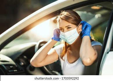 A young woman is putting a mask on her face, to avoid infection during flu virus outbreak and coronavirus epidemic, getting ready to go to work by car.