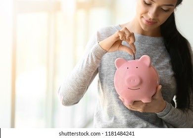 Young woman putting money into piggy bank near window