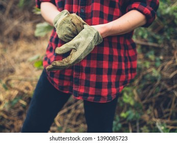 A young woman is putting on her gardening gloves in a garden