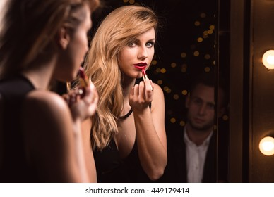 Young woman is putting on her make-up