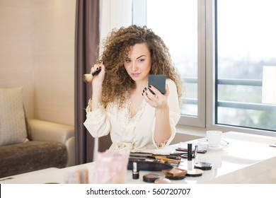Young woman putting some makeup