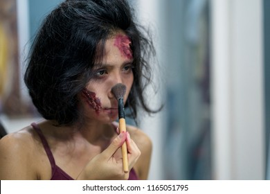 Young woman putting some special effects makeup for halloween party
