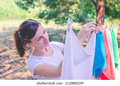Young woman are putting white laundry on a rope with plastic colorful clothespins to dry