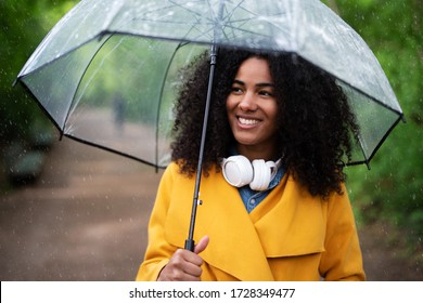 A young woman with rain jacket and umbrella outside in the rain