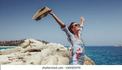 Young woman raise both hands at the beach
