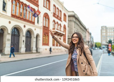 Young woman with raised arm waving for taxi in the city. Beautiful woman hailing a cab. Tourist woman hailing a taxi. Young woman hailing a taxi ride