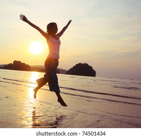 Young woman with raised hands running on wet sand