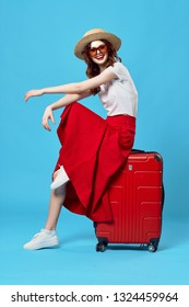 young woman with a raised leg sits on a red suitcase