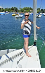 A young woman raises a glass in toast at the bow of a yacht