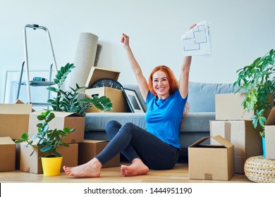 Young woman raising arms in joy while sitting in new apartment and holding floor plans