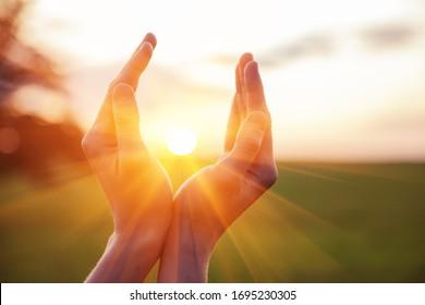 jeune femme levant les mains en priant au lever du soleil ou au coucher du soleil