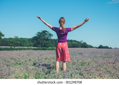 A young woman is raising her arms in a field of purple flowers
