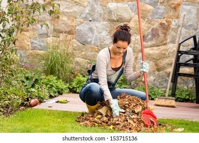Young woman raking leaves autumn pile garden veranda housework sweeping
