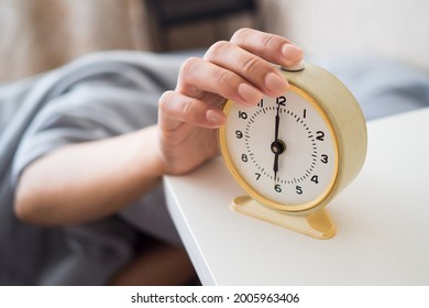 Young woman reach out one's hand Press the button to turn off the alarm clock in morning. A woman's hand presses the alarm button in the morning.