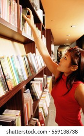 Young woman reaching for book on shelf