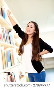 Young woman reaching for a book from a tall wall mounted book case smiling as she looks at the camera
