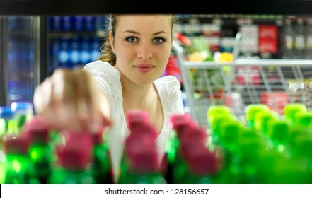 Young Woman reaching for a bottle in a Supermarket