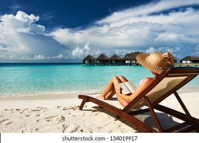 Young woman reading a book at the beach