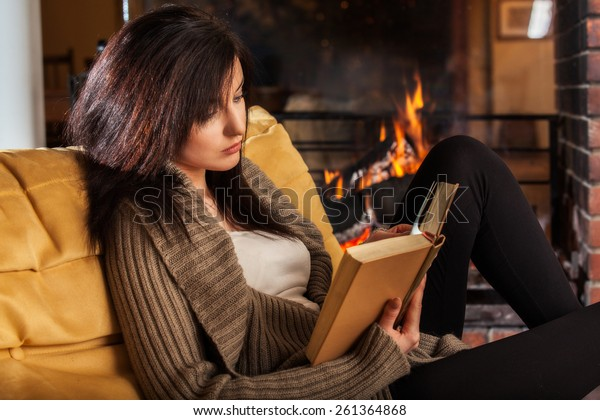 Young woman reading a book by fireplace