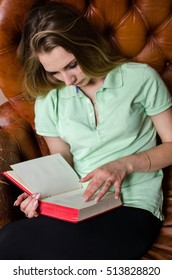 Young woman reading a book in the cafe